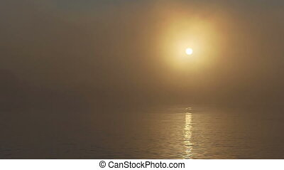 A dense fog covers the lake at a splendid sunset in summer