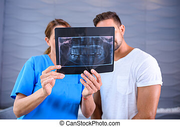A Dentist explaining the results of a XRAY to the patient