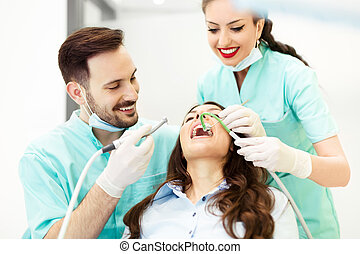A dentist with assistant working on a patient