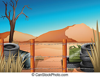 A desert with tires and a barbwire fence