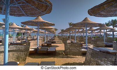 A deserted beach in the early morning, beach umbrellas and sun loungers are empty.