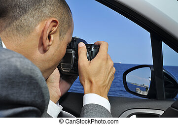 detective or a paparazzi taking photos from inside a car - a...