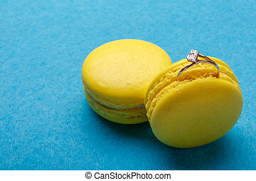 A diamond ring in yellow macaroon over blue background. the offer to marry. place for text