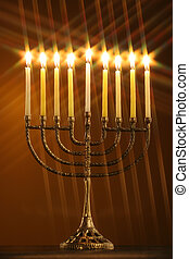 a different perspective on a traditional Hanukkah menorah with all candle lite with star filter on a gold background