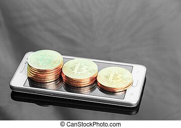 A digital money Bitcoin is placed on the front of an iPhone.