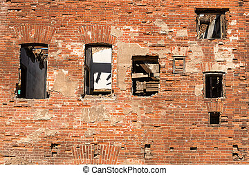 a dilapidated wall of an old two-story brick building with Windows without frames. ruin and chaos, oblivion