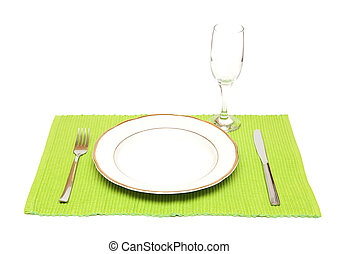 A dinner plate, knife, fork and wine glass on a green napkin