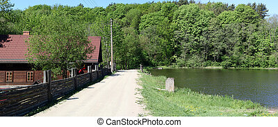A dirt sandy road leads to the Lithuanian village along the shore of a clean lake