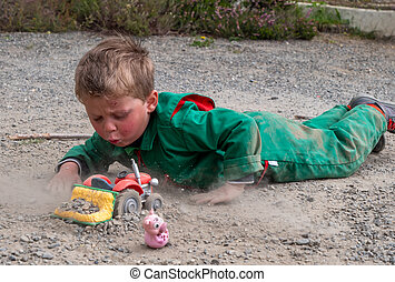 dirty child playing ground with tractor toy