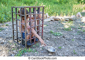 A dirty, undressed child sits in an iron cage outside - The ...