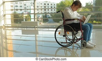 a disabled businessman on a wheelchair in a window with a drawing on a large sheet of paper, discusses work by phone