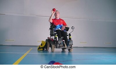 A disabled man in a wheelchair playing boccia. Balls in...