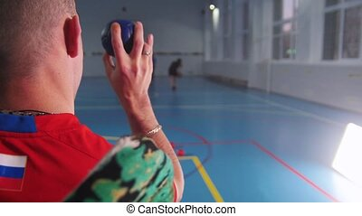 A disabled man in a wheelchair. Throwing a blue little ball....