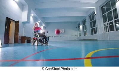 A disabled man in a wheelchair. Throwing a red little ball...