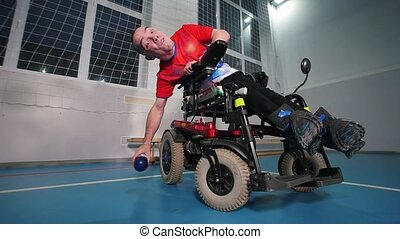 A disabled man in wheelchair. Throwing blue little ball....