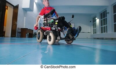 A disabled man in wheelchair. Throwing red little ball. Big...