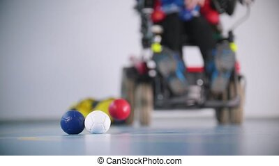 A disabled man in wheelchair. White, blue and red balls in...