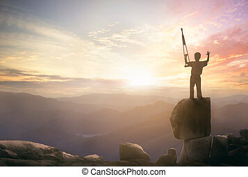 a disabled man standing up and raising his crutches over mountain sunset background