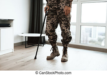 A disabled soldier is leaning on a crutch. He got up from the wheelchair and goes.