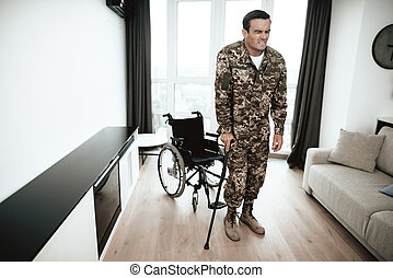 A disabled soldier is leaning on a crutch. He got up from the wheelchair and goes. It hurts.