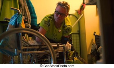 A disabled woman is transferred to a wheelchair in the corridor her apartment.