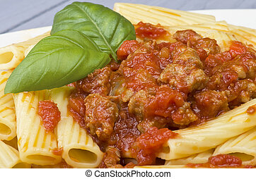 A dish of Maccheroni pasta with tomato souce and sausage