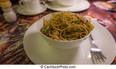A dish of noodles with chicken and vegetables.
