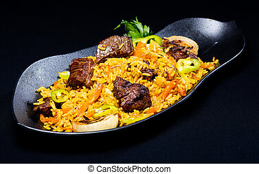 A dish of rice and meat on a black background.