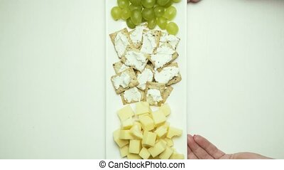 A dish with a snack is put on the table, two glasses for wine and poured. Top view