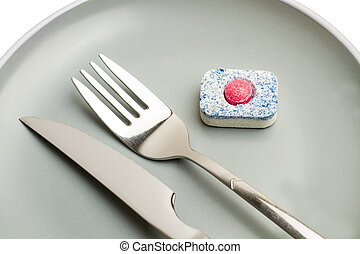 A dishwasher tablet on a gray plate