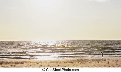 A distant view of a young girl who is standing on a sun-lit sandy beach looking at waves covering her feet.