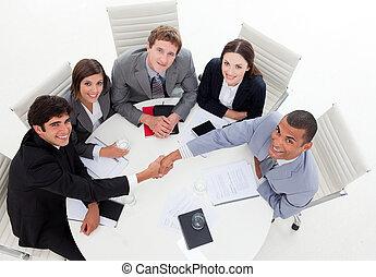 A diverse business group closing a deal