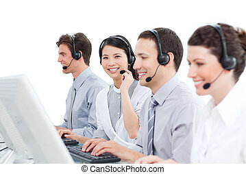 A diverse group of customer service agents working in a call center against a white background