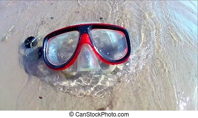 A diving mask lies on the sandy shore, waves of the sea surf on it on a sunny day. Slow motion Standard movement