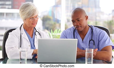 A doctor and a nurse looking at a laptop