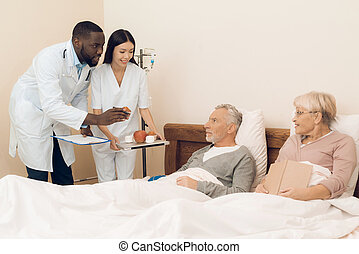 A doctor and a nurse offer an elderly couple an apple, marshmallows and muffins to bed.
