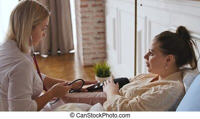A doctor in a white coat consults a woman at home during bed rest. Personal doctor. healthcare concept.