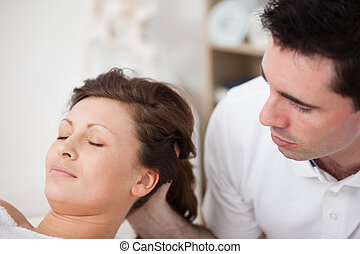 A doctor massaging the head of his patient while holding it