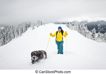 A dog and his mistress alone in the mountains with lots of snow