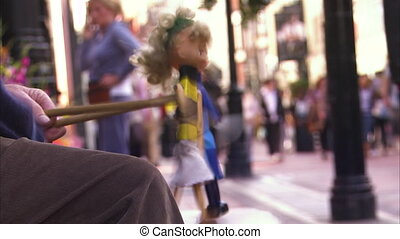 A doll and people on the side streets - A medium shot of a...