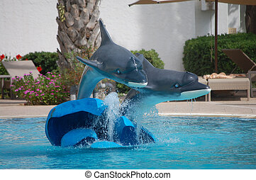 a dolphin statue in the hotel pool in summer