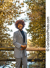 A Dominican girl with afro-red hair in an autumn session