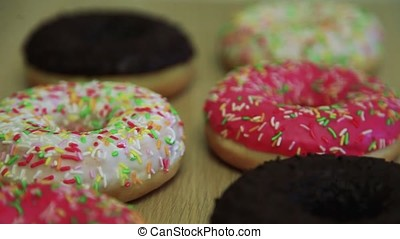 A donut in chocolate, a donut in a pink frosting, a donut in a cream glaze lie on a table. HD. Close-up