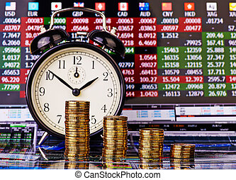 A downtrend stacks of golden coins with an alarm clock. Financial chart as background. Selective focus
