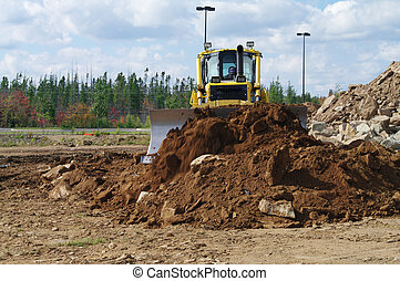 A dozer moving earth to level a pile of earth