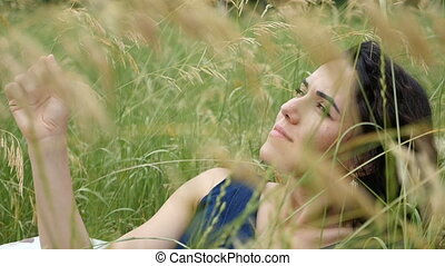 A dreaming brunette girl lies in a field on a sunny day in slo-mo