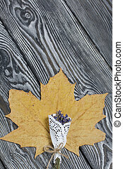 A dried maple leaf and a lavender bouquet on brushed black and white pine boards.