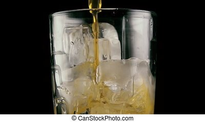 A drink flows into the glass with ice. Slow mo