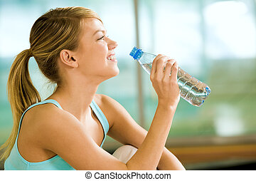 Profile of beautiful woman going to drink some water fron plastic bottle after workout