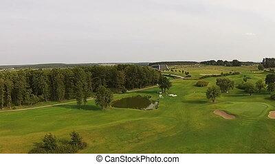 A drone flies over a green golf course